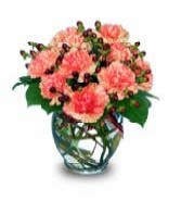 Orange carnations in a bouquet vase with berries and leather leaf
