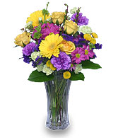 Purple carnations compliment gerberas, roses & other flowers in vase.