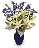 Hannukkah Flower Arrangment with blue delphinium, white lilies and blue vase