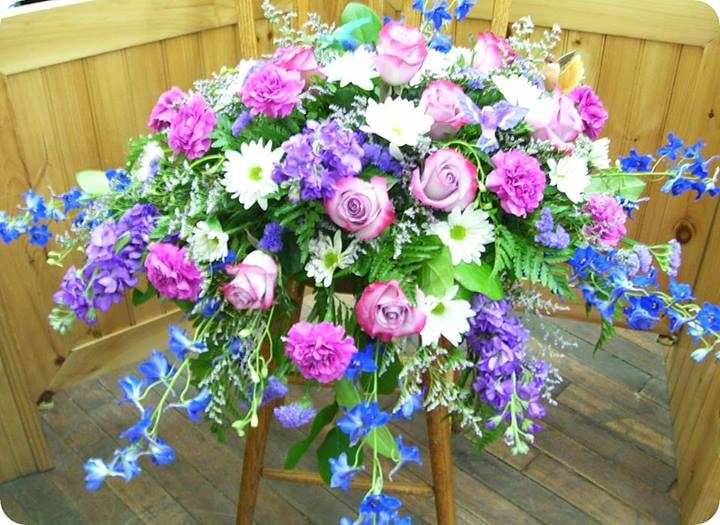 Purple and blue casket spray with hummingbirds by Coles Flowers in Middlebury, VT