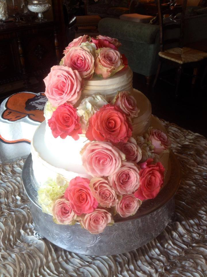 Roses cascading down a wedding cake from The Flower Shop in Pryor, OK
